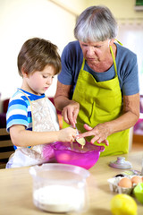 Senior woman helping grandson to cook and bake