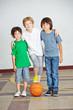 Drei Jungs mit Basketball auf Schulhof