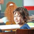 Lachender Junge sitzt in Schulklasse