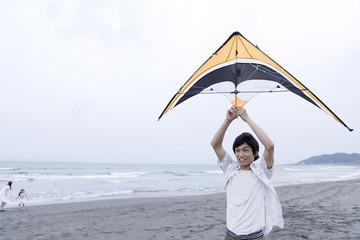 man holding sports kite on sandy beach