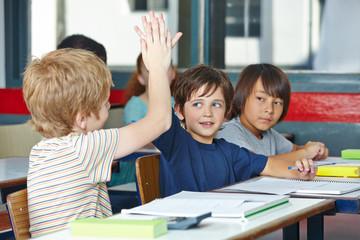 Schüler in Grundschule klatschen sich mit Händen ab