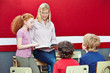 Lehrerin liest im Unterricht aus Schulbuch vor