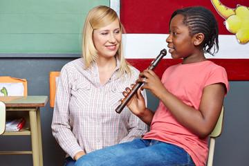 Mädchen in Musikschule lernt Flöte spielen