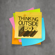 hand drawn THINKING OUTSIDE OF THE BOX on sticky note and textur