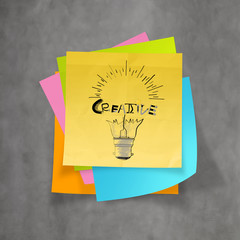 han drawn light bulb and CREATIVE word design on sticky note pa