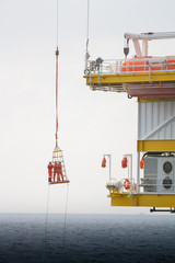 Workers are lifted by the crane to the offshore platform