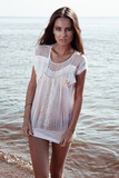 Young sexy brunette on the beach in wet t-shirt