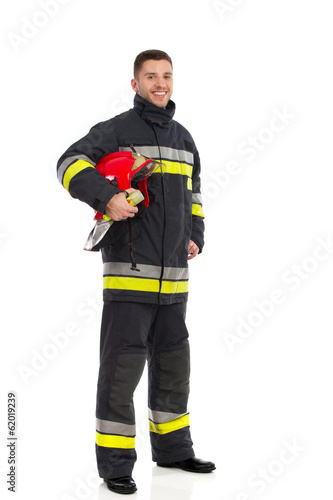 Firefighter posing with helmet under his arm - 62019239