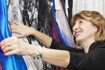 Happiness mature woman choosing a new dresses.