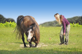 Woman with blond hair lays horse on green field
