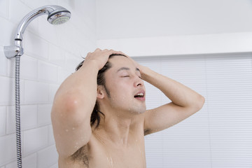 man shampooing his head in shower