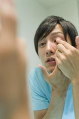 man putting on contact lens
