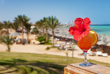 hibiscus and cocktail against tropical sea resort beach