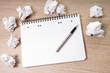 leerer Schreibblock mit Stift auf einem Tisch