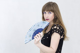 Young woman partly hidden behind a fan