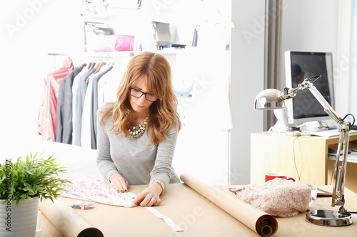 Mature fashion designer working in her studio