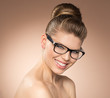 Joyful girl with retro hairdo wearing spectacles