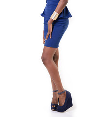 slim legs of african girl in blue dress and shoes, over white