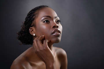 Beautiful young african woman posing at studio, face with hand p