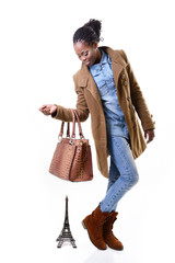 full length portrait of african girl in coat, jeans with bag loo
