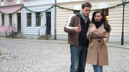 Couple looking for directions on cellphone and tablet pc