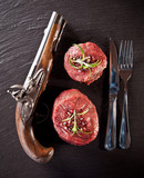 Fresh raw beef steaks on black stone