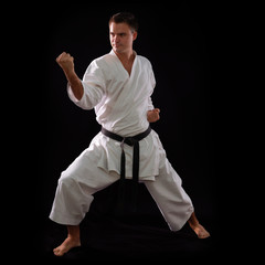 karate man with black belt posing, champion of the world on blac