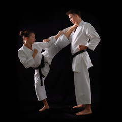 fighting karate couple, man and woman with black belts - champio