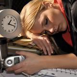 Erschöpfte Frau schläft im Büro