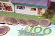 Eigenheim mit Euromünzen und Geldschein