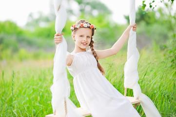 Girl in white dress sitting on a swing