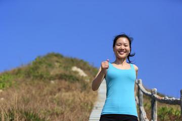 fitness woman running on mountain stairs to peak
