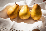 Golden pears on the white vintage tablecloth
