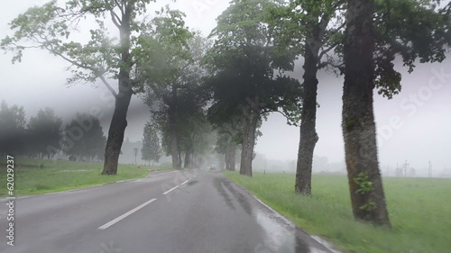 strong rain fall on car automobile windscreen  driving on road