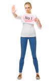 "Young girl in blue jeans with ""No"" placard"