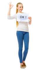 "Young girl in blue jeans with ""Ok"" placard"