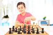 Little boy playing chess seated on a table