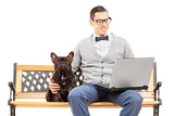 Young man sitting with his dog and working on laptop