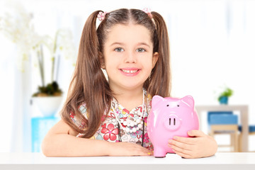 Little girl sitting at table and holding a piggybank indoors