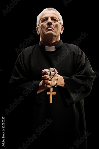 Catholic reverend holding a wooden cross