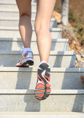 fitness woman legs running up on mountain stairs to peak