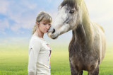 Horse cuddle with woman, summer background with green grass