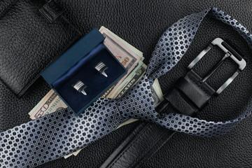 Tie, belt, wallet, cufflinks, money lying on the skin