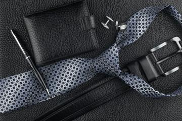 Tie, belt, wallet, cufflinks, pen lying on the skin