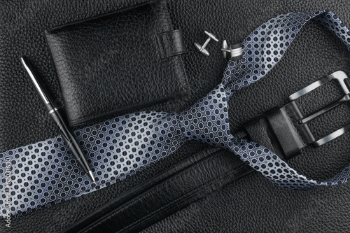Tie, belt, wallet, cufflinks, pen lying on the skin