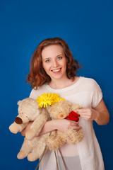 Радостная девушка с цветами и игрушками на синем фоне
