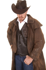 Cowboy in vest and duster hat cover eyes look down