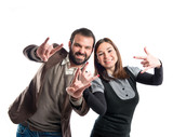 Couple doing the horn sign over white background