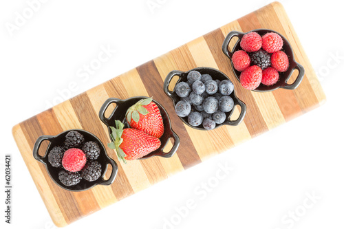 Varieties of fresh berries in individual dishes