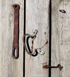 Rusty metal hook in old wooden door